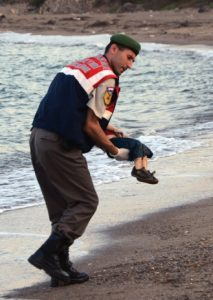 A paramilitary police officer carries the lifeless body of a  migrant child after a number of migrants died and a smaller number  were reported missing after boats carrying them to the Greek island of Kos capsized, near the Turkish resort of Bodrum early Wednesday, Sept. 2, 2015. (AP Photo/DHA) TURKEY OUT
